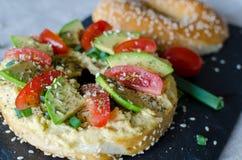 Bagel med hummus, avokadoskivor, kryddor, salladsl?ken, tomater k?rsb?r och sesamfr? p? svartstenskrivbordet close upp royaltyfria bilder