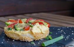 Bagel med hummus, avokadoskivor, kryddor, salladsl?ken, tomater k?rsb?r och sesamfr? p? svartstenskrivbordet close upp royaltyfri foto