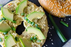 Bagel- med hummus, för avokadoskivor, krydda-, salladslök- och sesamfrö på svarten stenar skrivbordet close upp Top besk?dar arkivfoton