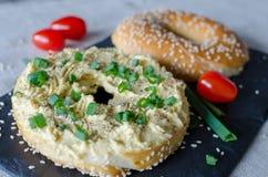 Bagel med hummus, kryddor, salladsl?ken, tomater k?rsb?r och sesamfr? p? svartstenskrivbordet close upp royaltyfri fotografi