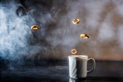 Bagel mit Mohn fliegen über einen Tasse Kaffee Stockfoto