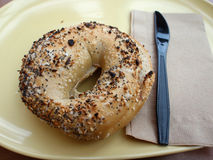 Bagel and Plastic Knife on a yellow plate Stock Images