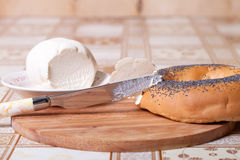 Bagel with poppy seeds and soft cheese on a wooden board Royalty Free Stock Photos