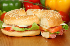 Bagel with salami. Tomatoes, cheese and salad royalty free stock image