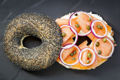 Bagel with Salmon and Cream Cheese. Bagel with smoked salmon, cream cheese, capers and red onion.  Overhead view, on dark slate Royalty Free Stock Images