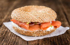 Bagel with Salmon on wooden background Royalty Free Stock Image