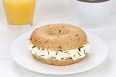 Bagel sandwich for breakfast with cream cheese, orange juice and Stock Photo
