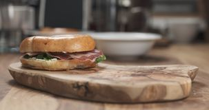 Bagel sandwich with coppa and cream cheese on wood board. Wide photo Royalty Free Stock Photo