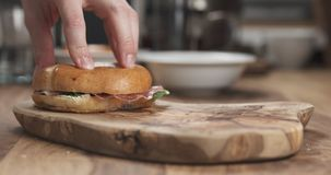 Bagel sandwich with coppa and cream cheese on wood board. Wide photo Stock Images