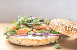 Bagel sandwich with creame cheese, salmon,onion,tomato,greens,ch. Ives close-up on a wooden background. Delicious bagel, golden bake color, soft inside, crispy stock photo