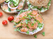 Bagel sandwich with creame cheese, salmon,onion,tomato,greens,ch. Ives close-up on a wooden background. Delicious bagel, golden bake color, soft inside, crispy stock images