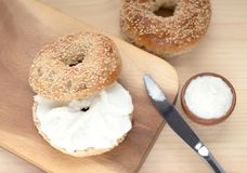Bagel sesame with spread cream cheese close-up on a wooden cut. Board royalty free stock images