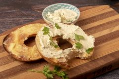 Bagel topped with cream cheese and chives. Taken with copy space stock photo