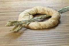Bagel and wheat. A bagel and some wheat on a bamboo mat Royalty Free Stock Photos
