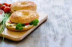 Bagels με το τυρί, τις ντομάτες και τα φρέσκα κρεμμύδια κρέμας για το υγιές πρόχειρο φαγητό Στοκ εικόνα με δικαίωμα ελεύθερης χρήσης