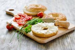 Bagels με το τυρί, τις ντομάτες και τα φρέσκα κρεμμύδια κρέμας για το υγιές πρόχειρο φαγητό Στοκ Εικόνες
