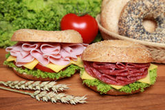 Bagels. Two fresh bagels with salami and ham aswell as cheese, tomatos and lettuce royalty free stock images