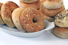 Bagels. Assorted bagels in dish and stacked in background Royalty Free Stock Photos