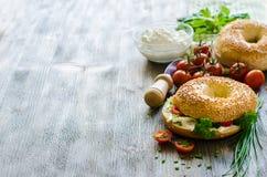 Bagels avec le fromage fondu, les tomates et la ciboulette pour le casse-croûte sain Photographie stock