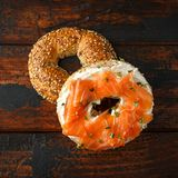 Bagels breakfast sandwich with Cream cheese and salmon on wooden table.  royalty free stock photo
