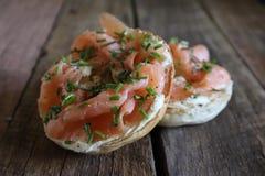 Bagels com salmão fumado e queijo creme na placa de madeira imagens de stock royalty free