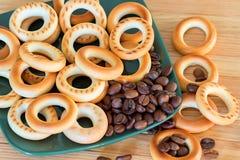 Bagels corado e feijões de café em uma placa Foto de Stock