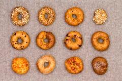 12 bagels différents de spécialité montrés sur le coton Photo libre de droits