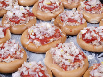 Bagels and forcemeat. Some bagels zapoleny forcemeat and strewed with onions on the pro-twin Stock Images