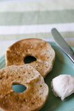 Bagels on plate. Toasted bagels on plate with cream cheese and knife stock images