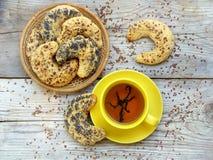 Bagels polvilhados com as sementes de papoila e as sementes de linho em uma cesta e um copo amarelo do chá Foto de Stock