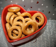 Bagels on red plate of heart shape on gray background. Stock Photos