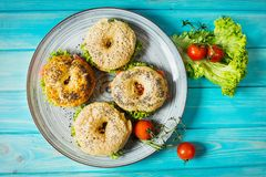 Bagels with salmon, vegetables, cream-cheese on blue wood background Royalty Free Stock Photo