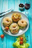 Bagels with salmon, vegetables, cream-cheese and glass of red wine on blue wood background Royalty Free Stock Photos
