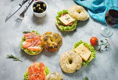 Bagels with salmon, vegetables, cream-cheese and glass of red wine on grey concrete background Royalty Free Stock Images