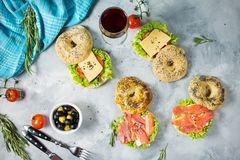 Bagels with salmon, vegetables, cream-cheese and glass of red wine on grey concrete background Stock Image