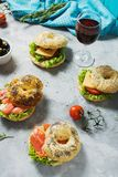 Bagels with salmon, vegetables, cream-cheese and glass of red wine on grey concrete background Royalty Free Stock Photo