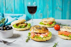 Bagels with salmon, vegetables, cream-cheese and glass of red wine on grey concrete background Stock Images