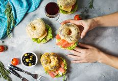 Bagels with salmon, vegetables, cream-cheese and glass of red wine on grey concrete background. Woman hands hold bagel Royalty Free Stock Image
