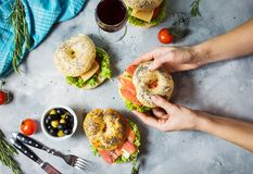 Bagels with salmon, vegetables, cream-cheese and glass of red wine on grey concrete background. Woman hands hold bagel Royalty Free Stock Photos
