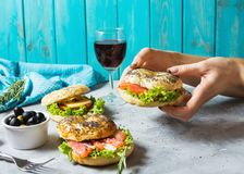 Bagels with salmon, vegetables, cream-cheese and glass of red wine on grey concrete background. Woman hands hold bagel Royalty Free Stock Photo