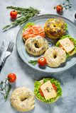 Bagels with salmon, vegetables, cream-cheese on grey concrete background Stock Photos