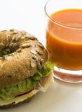 Bagelsandwich und Karottensaft stockfotos