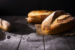 Bageri - guld- lantliga vresiga loaves av bröd och bullar på svart bakgrund royaltyfri foto