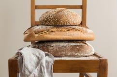 Bageri - hög av lantliga vresiga loaves av bröd arkivbilder