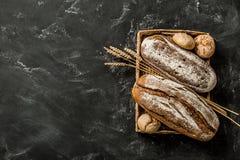 Bageri - lantliga vresiga loaves av bröd och bullar på svart royaltyfri foto