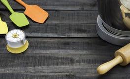Bageri- och matlagninghjälpmedel med köktimekeeping på den wood tabellen Royaltyfri Fotografi