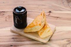Bageri och svarttekanna på trätabellen Royaltyfri Bild