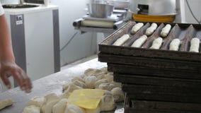 Bageriarbetare som gör mjuka rullar i industriellt kök stock video
