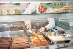 Bageriarbetaren som ut tar den ljusbruna kakan från, ställer ut arkivfoto