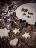 Bagerikakadeg med klippformen på köksbordet royaltyfria foton